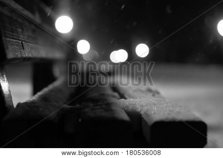 View of bench and shining lantern through snowing