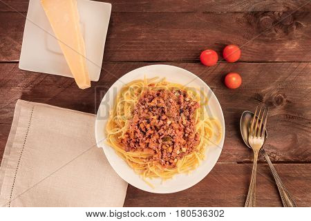 An overhead photo of a plate of pasta with meat and tomato sauce, a piece of cheese, and a place for text