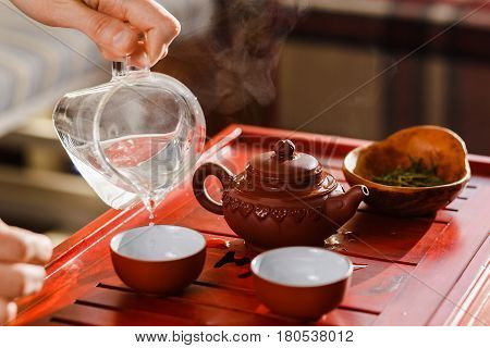 The tea ceremony. Woman pours tea in a tea bowl. Close-up.