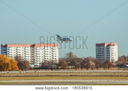 Kiev Region Ukraine - November 13 2011: Cessna 510 Citation Mustang is landing in the airport with some buildings on the background