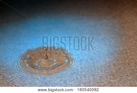 stiffened water drop falling on a water surface,Blue and brown tones