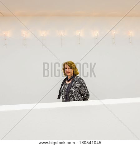 attractive lady walking on a balcony in the museum with white walls