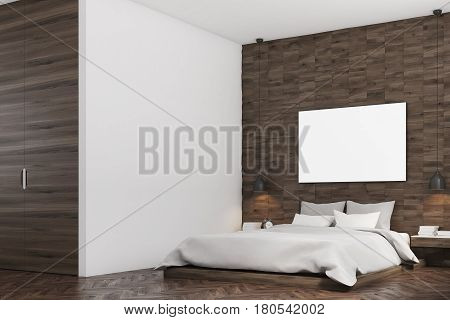 Side view of a bedroom with dark wood walls a double bed with gray bedding and a large horizontal poster hanging above it. 3d rendering mock up