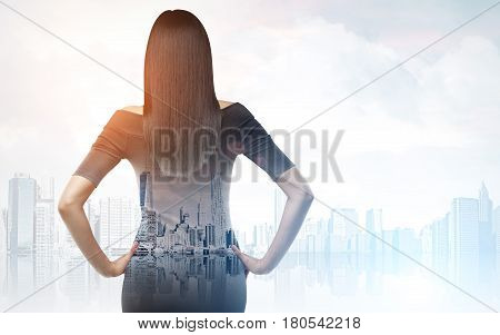 Rear view of businesswoman wearing a black dress and standing with her hands on the waist looking at a foggy city panorama. Toned image. Double exposure. Mock up