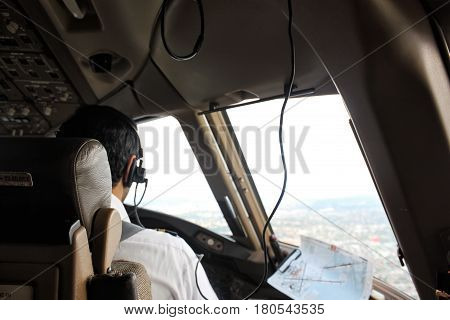 Pilot sitting on a jumpseat in flight deck with headphones communicating with tower looking through a aircraft window just before landing