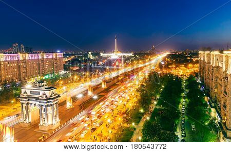 Triumphal Arch, Victory Park and the alley of fountains in Moscow, blurry lights of cars on multi-lane highways and road junction at night in Moscow