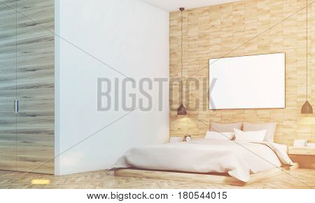 Side view of a bedroom with light wood walls a double bed with gray bedding and a large horizontal poster hanging above it. 3d rendering mock up toned image
