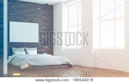 Side view of a bedroom with dark wooden walls a double bed with gray bedding and a large horizontal poster hanging above it. 3d rendering mock up toned image