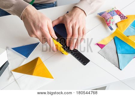 closeup on men hands of tailor, who is sitting behind a white desk and cut out colorful pieces of fabrics with rotary cutters for sewing patchwork items. Handwork and hobby concept.