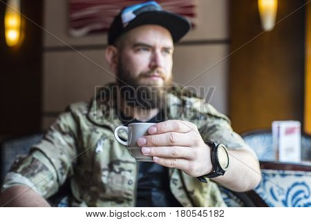A Bearded Guy. A Guy With A Cup Of Coffee In No Focus.