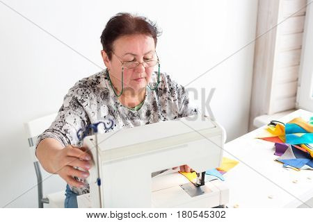 patchwork and quilting at the workshop of a tailor woman on white background - elderly tailor woman with glasses sews on the sewing machine scraps of colorful fabrics. Hobby and sewing concept.