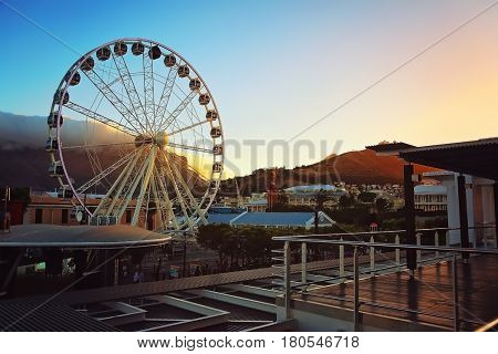 Cape Town South Africa. View at the Waterfront giant observation Wheel during sunset. Wheel has 30 air-conditioned cabin which offer 360 degree panoramatic view of Cape Town from iconic and vibrant V&A Waterfront precinct. You can see Table Mountain at th