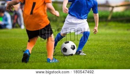 Two young boys in orange and blue jersey shirts kicking soccer match on the green grass field. Summertime sport soccer activity for kids. Children running and competing for the ball.