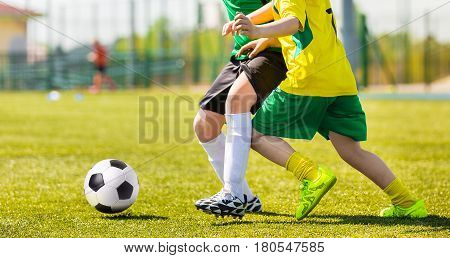 Training and football match between youth soccer teams. Young boys playing soccer game. Hard competition between players running and kicking soccer ball. Final game of football tournament for kids.