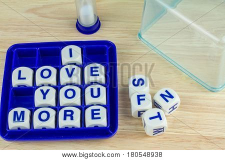 Wording Game with Blue Alphabets on White Cube Blocks say i LOVE YOU MORE in Blue Tray on Wooden Surface Background with Sand Timer and Clear Cover in the back