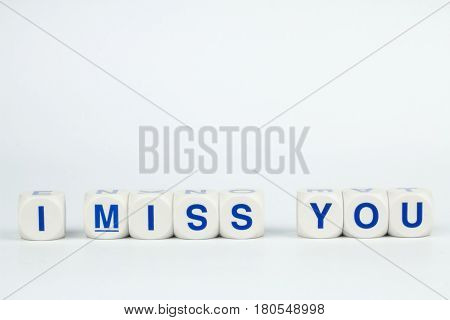 Blue Alphabet on White Cube Blocks say I MISS YOU in White Background with Shadow