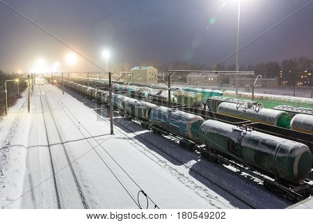 Freight cars on the sorting cargo station in the light of searchlights at night in winter in Russia