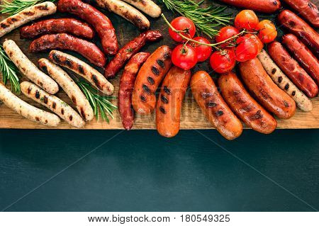 Grilled sausages on a board lighten up by summer sunny warm light space for a text view from above