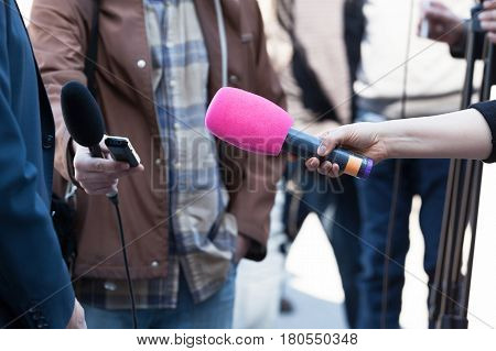 Reporters or journalists holding microphones conducting television interview. News conference.