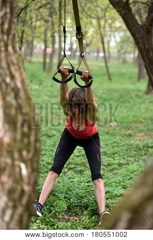 Young Attractive Woman Does Body Stretching With Trx Fitness Straps