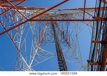 bottom view of telecommunication tower with blue sky for radio television and telephony