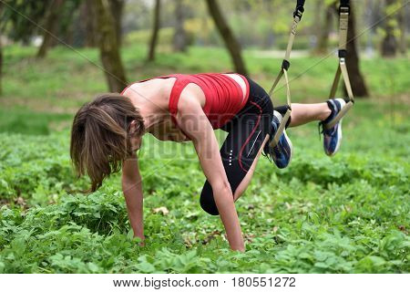 Beautiful Young Woman Doing Trx Exercise With Suspension Trainer Sling In The Outdoors