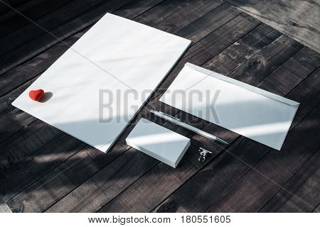 Photo of blank stationery set on wooden table background. Sheet of paper letterhead business cards envelope eraser and pen. Mockup for branding identity. ID template.