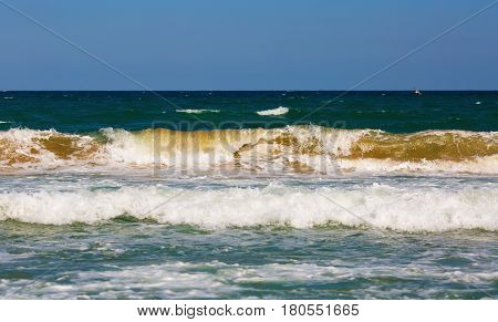 Ocean waves rolls ashore. Sea surf on a clear sunny summer day. Sea waves with foam and spray rolling ashore. Shallow depth of field. Selective focus.
