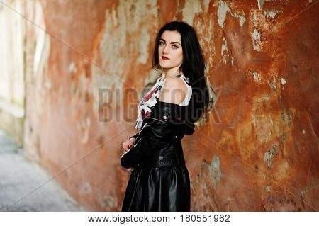 Young Goth Girl On Black Leather Skirt And Jacket Against Grunge Wall.