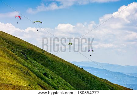 Skydivers fly over the mountains. Parachute extreme sport