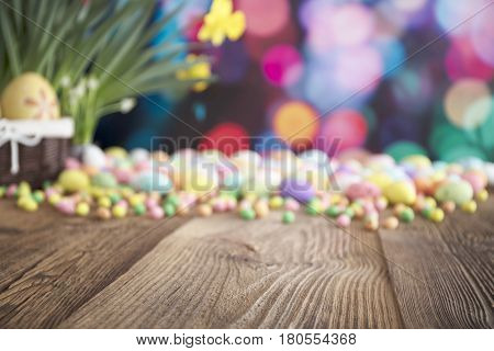 Easter theme. Bouquet of yellow jonquils. Easter eggs. Colorful bokeh, place for typography and logo. Rustic wooden table.
