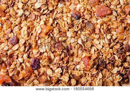 Homemade granola with honey, oatmeal, nuts, raisin, cranberry and dried apricots for background, top view, horizontal