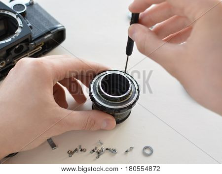 The engineer-technician checks the optics and carries out maintenance and cleaning of the broken vintage lens of the camera. Top view of the workplace and the hands of the engineer.
