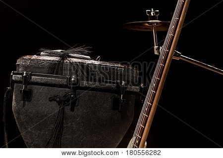 musical instruments, acoustic guitar and bass guitar and percussion instruments drums on a black background, the music concept