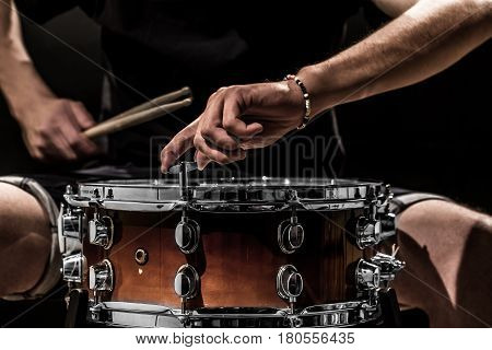 man adjusts a percussion instrument closeup on black background musical concept with the working drum