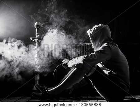 a man smokes a hookah on a black background, holiday concept, beautiful lighting