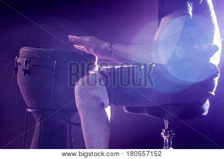 man playing the djembe, african drum, closeup on black background musical concept, beautiful lighting on the stage