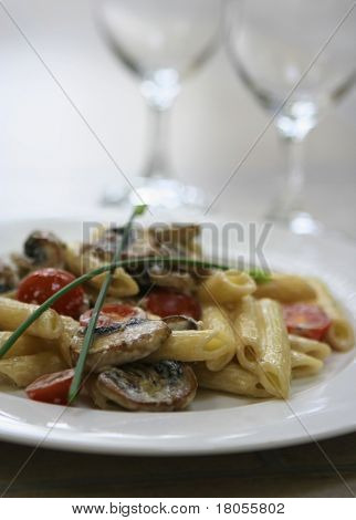 A plate of mushroom pasta with tomatoes and two empty wine glasses