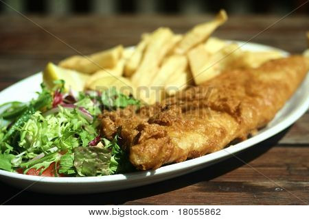 A plate of battered fish and chips with fresh green salad on wooden table