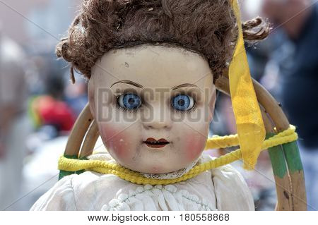 a close-up shot of an old dirty doll head with grunge evil face like from horror movie at a flea market in Lisbon, Portugal