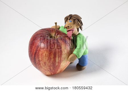 Man made of modelling clay licking and hugging a red apple on a white background