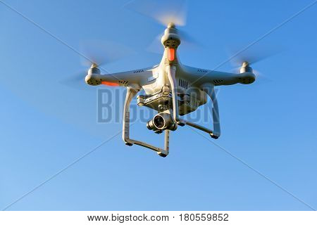 Drone quad copter with onboard high resolution digital camera flying in the blue sky