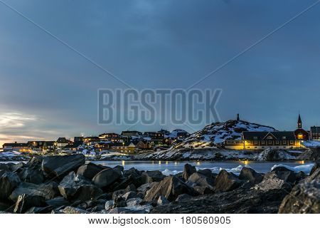 Nuuk city old harbor sunset view with stones and icebergs Greenland