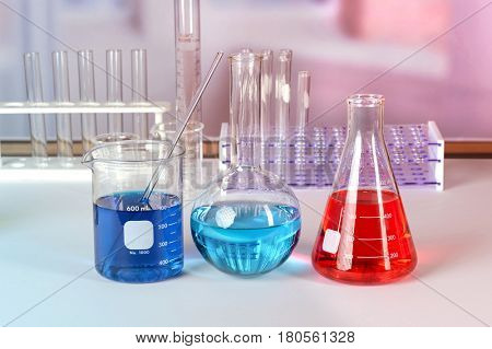 Laboratory glassware with fluids of different colors on white table