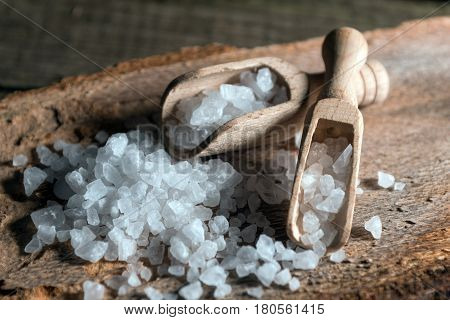 Cyprus sea salt flakes over bark on wooden background