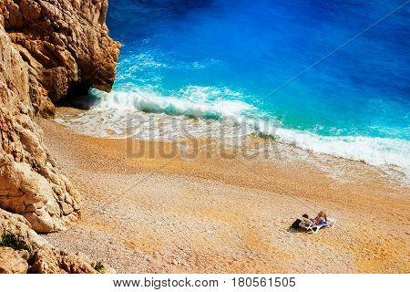 Tourist sunbathing on a deserted beach in the Mediterranean Sea