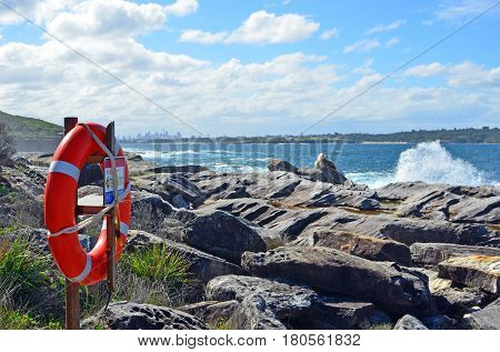 Lifesavers ring on rock platforms on rocky coastline with breaking waves and Sydney city skyline in the background, New South Wales, Australia.