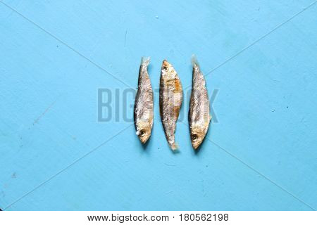 Sun dried fish on a blue surface