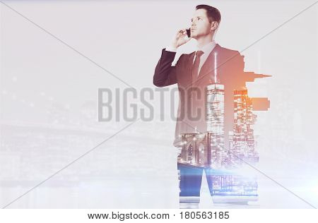 Side view of handsome young businessman talking on the phone on city background with copy space. Communication concept. Double exposure