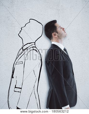 Businessman and drawn human outline standing back to back on concrete background